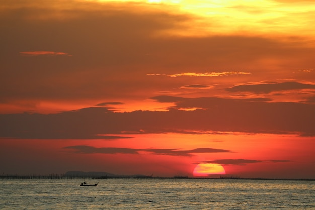 Sonnenuntergang auf hinterer abendwolke des roten gelben himmels über horizontmeer