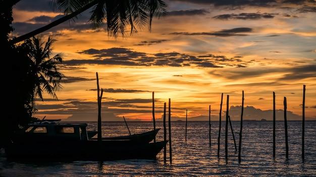 Sonnenuntergang auf kri island. einige boote im vordergrund. raja ampat, indonesien, west papua.