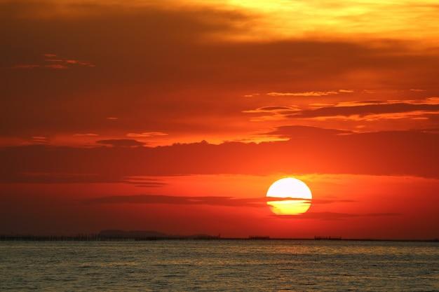 Sonnenuntergang auf roter gelber himmelrückseite weicher abendwolke über horizontmeer