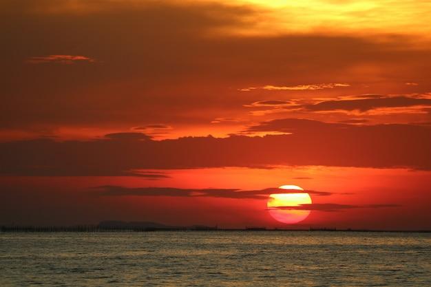 Sonnenuntergang auf weicher abendwolke des roten orange himmels zurück über horizontmeer