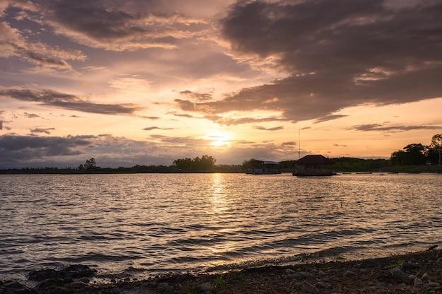 Sonnenuntergang, der auf huai mai teng-reservoir mit geplätscherter welle scheint