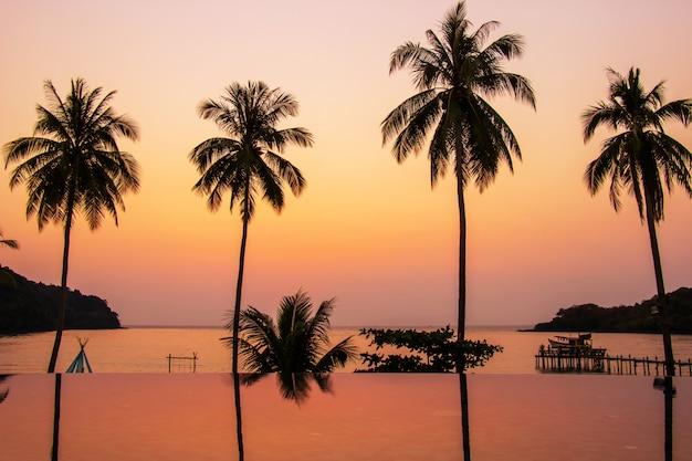Sonnenuntergang, der über den wasseroberflächenvordergrund mit kokosnussbäumen bereich ao bang bang am koh kood nachdenkt.
