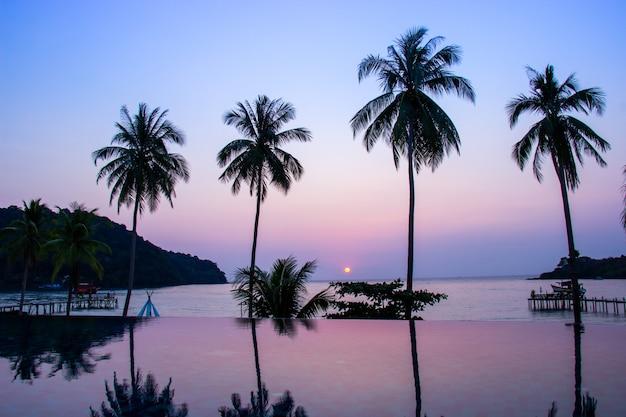 Sonnenuntergang, der über den wasseroberflächenvordergrund mit kokosnussbaumbereich ao knall bao nachdenkt