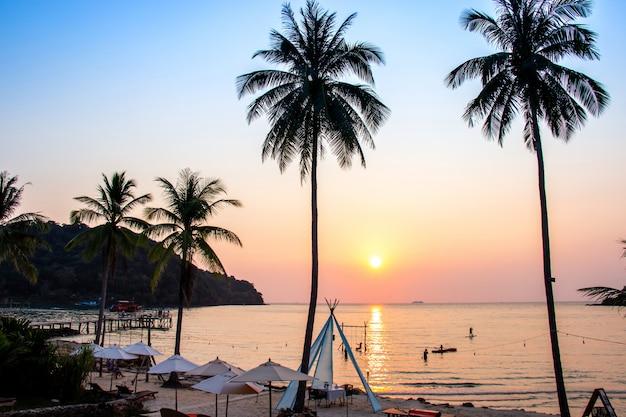 Sonnenuntergang, der über den wasseroberflächenvordergrund mit kokosnussbaumbereich ao-knallbao bei koh kood nachdenkt.