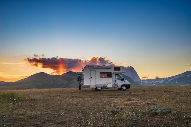 Sonnenuntergang dramatischer himmel über wohnmobil im hochland campo imperatore, abruzzen, italien. epische wolken über einzigartigem hochland und felsiger berglandschaft, alternatives vanlife-ferienkonzept.