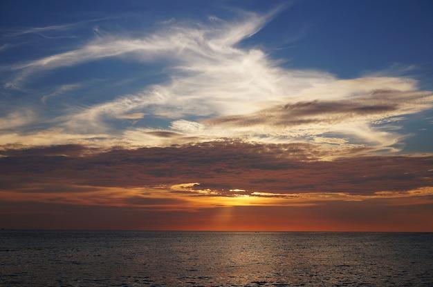 Sonnenuntergang durchdringt den himmel in karon beach, phuket.,