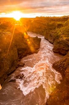 Sonnenuntergang gesehen von der holzbrücke des barnafoss-flusses, island.