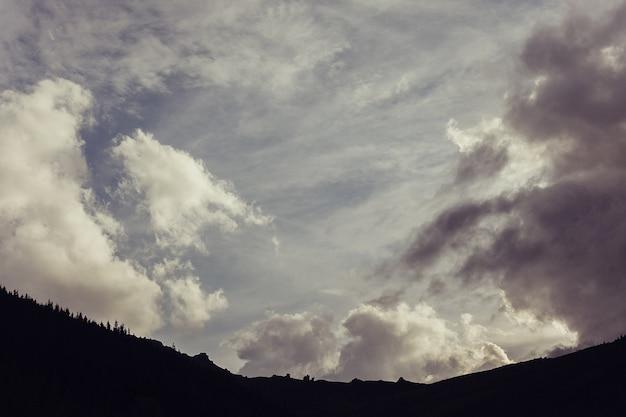 Sonnenuntergang hinter fichten auf einem üppig grünen hang. zelte und rauch in der ferne. mehrere wolken am orangefarbenen himmel bei sonnenuntergang. warmer sommerabend. marmarosh-gebirge, karpaten, ukraine