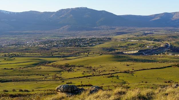 Sonnenuntergang in den bergen mit kleinen dörfern am berghang, kühen und bauernhöfen auf dem land. navacerrada madrid. spanien.