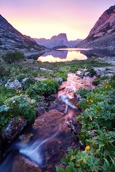 Sonnenuntergang in den bergen nahe fluss. sonnenlicht spiegelt sich auf berggipfeln. goldenes licht