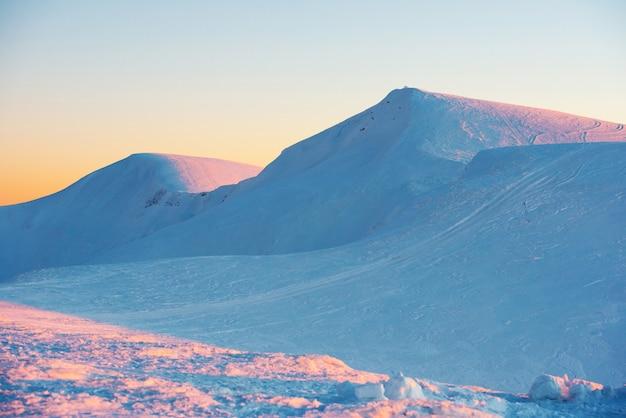 Sonnenuntergang in den mit schnee bedeckten winterbergen Premium Fotos
