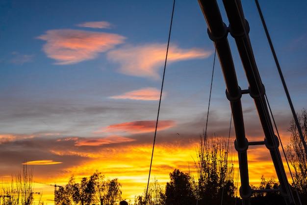 Sonnenuntergang in einer mediterranen stadt mit der silhouette der metallstruktur einer hängebrücke