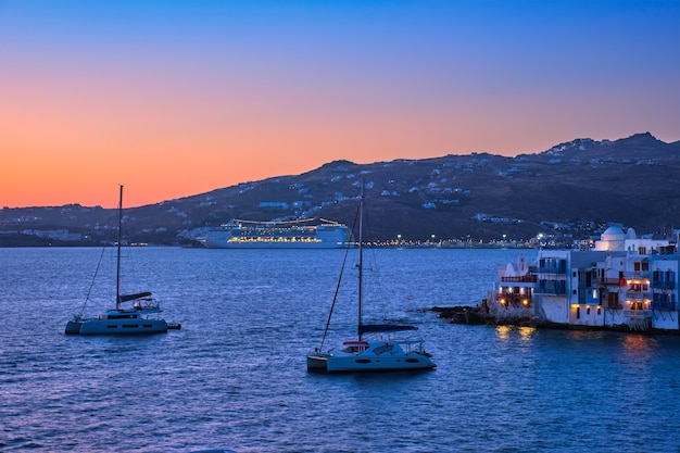Sonnenuntergang in mykonos griechenland mit kreuzfahrtschiff und yachten im hafen