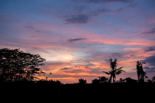 Sonnenuntergang mit der silhouette eines landhauses und von bäumen