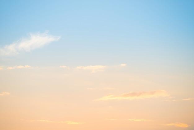 Sonnenuntergang mit sonne und wolken am blauen und orangefarbenen pastellhimmel