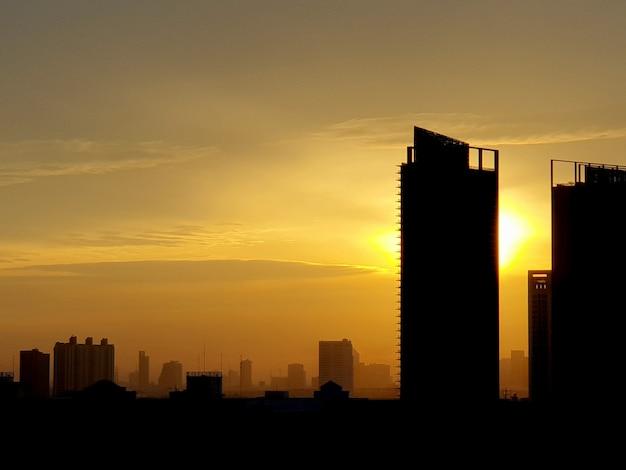 Sonnenuntergang mit wolken am himmel hinter hohen gebäudetürmen über der stadt