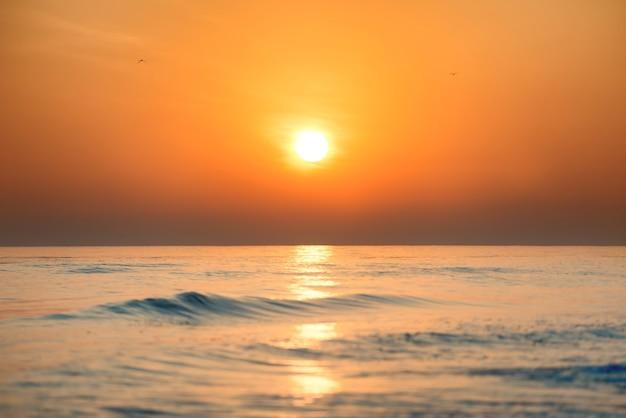 Sonnenuntergang oder sonnenaufgang über dem meer mit großer sonne am wunderschönen dramatischen himmel