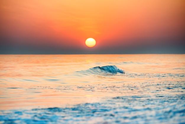 Sonnenuntergang oder sonnenaufgang über dem meer mit sonne am wunderschönen dramatischen himmel