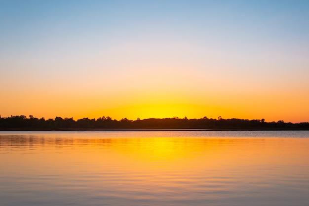 Sonnenuntergang reflexion lagune. wunderschöner sonnenuntergang hinter den wolken und blauer himmel über der lagunenlandschaft