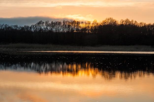 Sonnenuntergang spiegelte sich im wasser des flusssees