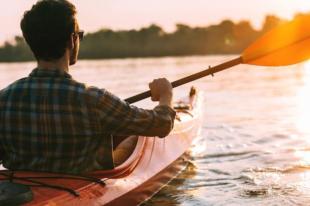 Sonnenuntergang treffen. rückansicht eines jungen mannes, der auf dem see mit sonnenuntergang im hintergrund kajak fährt