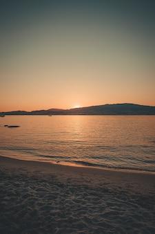 Sonnenuntergang über dem berg vom strand