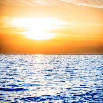 Sonnenuntergang über dem blauen meer mit orangefarbenem himmel und wolken