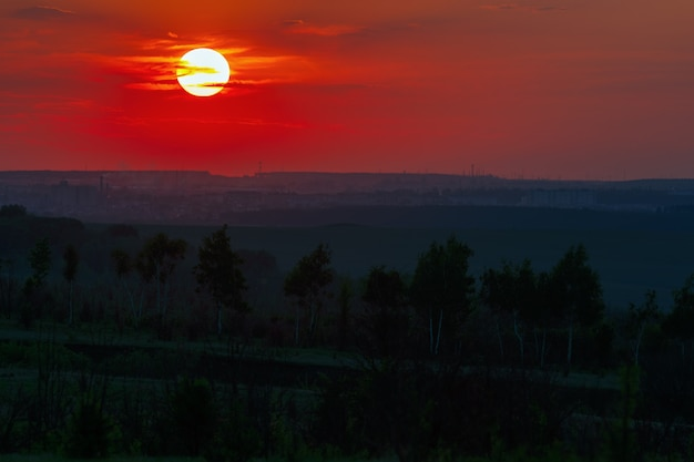 Sonnenuntergang über dem horizont bei bewölktem himmel.