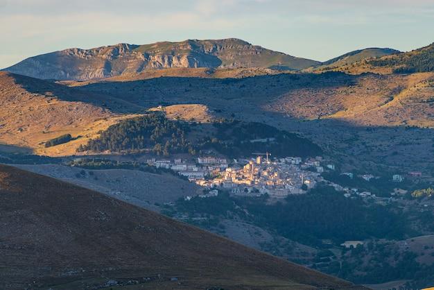 Sonnenuntergang über dem mittelalterlichen dorf thront auf einem hügel, abruzzen, italien. nationalpark gran sasso, berglandschaft, tourismusziel.