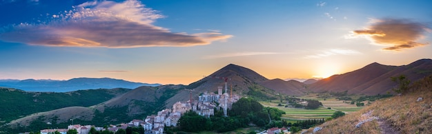 Sonnenuntergang über dem mittelalterlichen dorf thront auf einem hügel, santo stefano di sessanio, abruzzen, italien. romantischer himmel und wolken über berglandschaft, tourismusziel.