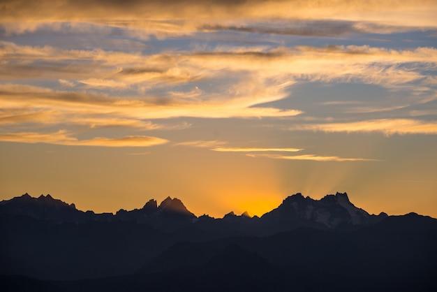 Sonnenuntergang über den alpen. bunter himmel, bergspitzen der großen höhe mit gletschern, nationalpark massif des ecrins, frankreich.