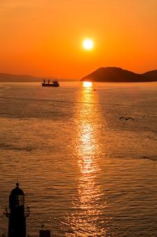 Sonnenuntergang über der adria und seinen booten, die in den reflexionen am eingang zum hafen von split in kroatien spielen.