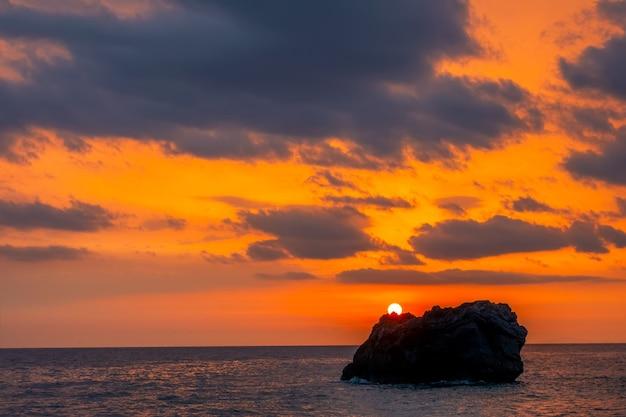 Sonnenuntergang über einem einsamen felsen in einem ruhigen meer. tolle farben am bewölkten himmel