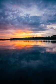 Sonnenuntergang über einem fluss mit einem orangefarbenen himmel am horizont