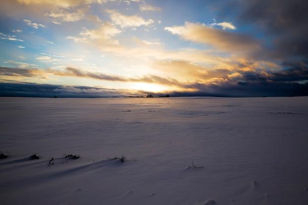 Sonnenuntergang über einem landwirtschaftlichen feld im winter, das feld ist mit einer weißen, flauschigen schneeschicht bedeckt, driftet mit schnee