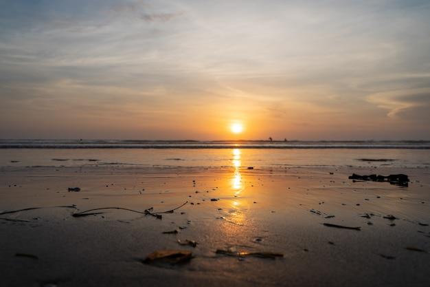 Sonnenuntergang über einem meer mit den wellen, die auf dem strand brechen