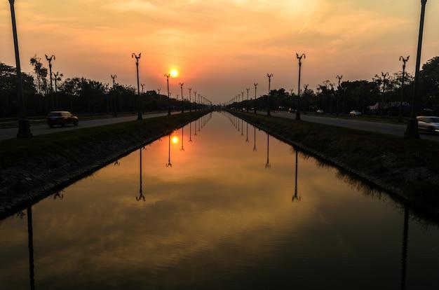 Sonnenuntergang über einer autobahn utthayan road und reflexion über den fluss