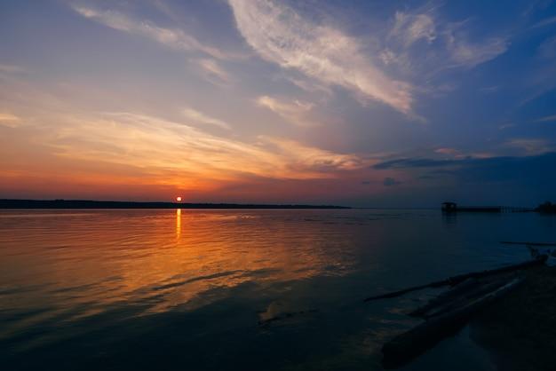 Sonnenuntergang über fluss und schönem himmel am sommerabend und am schattenbild des piers
