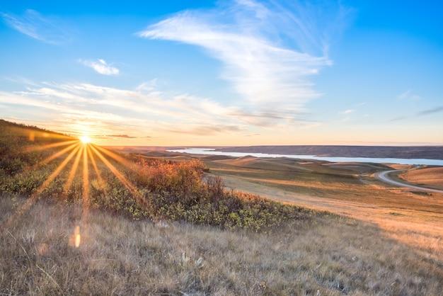 Sonnenuntergang über herbstlaub auf einem abhang, der see diefenbaker in saskatchewan übersieht