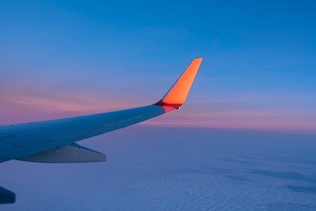 Sonnenuntergang über himmel und flügel des flugzeugs, ansicht vom flugzeugfenster