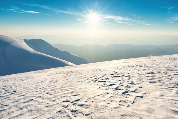Sonnenuntergang über hügeln und bergen mit schnee
