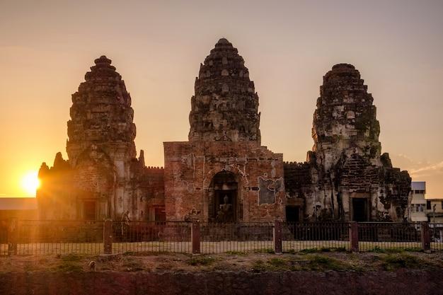Sonnenuntergang über khmer-art des alten denkmals (phra prang sam yot) mit affen