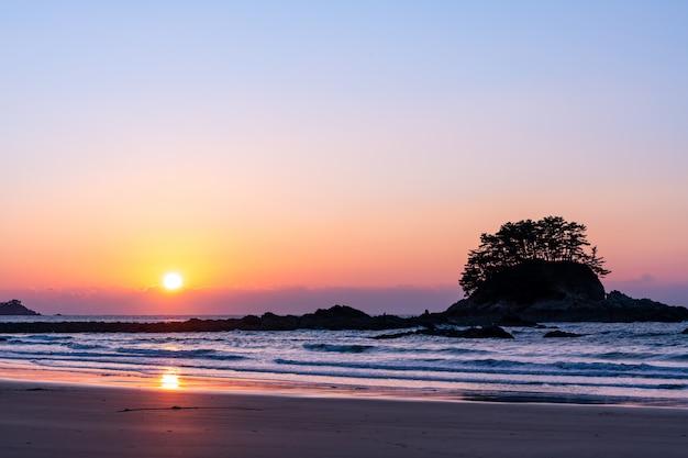 Sonnenuntergang über meer mit wellen und kleiner insel