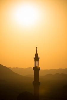 Sonnenuntergang über wüste mit moslemischer moschee