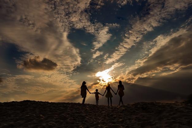 Sonnenuntergang und familiensilhouette mit sonnenuntergang im hintergrund