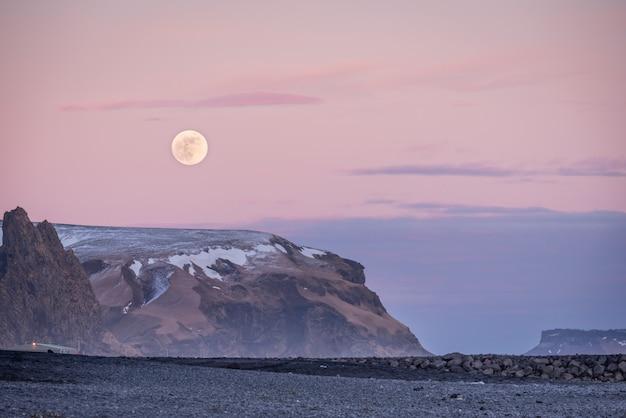 Sonnenuntergang und mond steigen über bergen und viks schwarzem sandstrand in island in der dämmerung