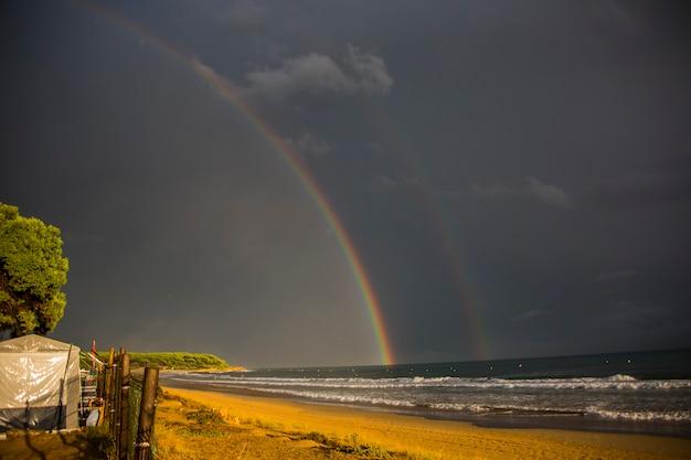 Sonnenuntergang und regenbogen im strand von platja llarga
