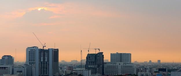 Sonnenuntergang und wolkenhintergrund am abend, stadt im stadtzentrum gelegen mit sonnenunterganghimmel