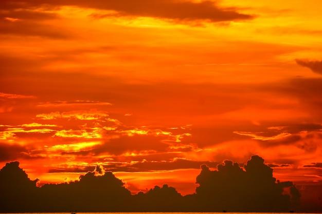 Sonnenuntergang zurück auf letzter hellroter orange himmelschattenbildwolke