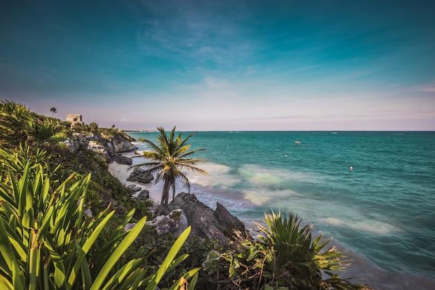 Sonnenuntergangansicht an den maya-ruinen von tulum an der tropischen küste. el castillo tempel am paradiesstrand. maya-ruinen von tulum, quintana roo, mexiko.